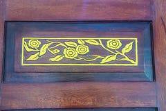在红色木门事假的被雕刻的金黄花纹花样 免版税图库摄影