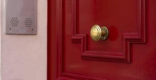 在红色木门的发光的铜门把手 库存图片
