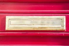在红色木门的古典老邮箱 免版税库存图片