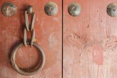 在红色木门的老金属圆环把柄 库存照片