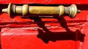 在红色木门的老黄铜把柄 免版税库存照片