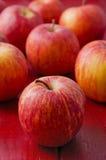 在红色木头的苹果。垂直 库存照片