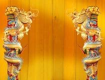 在红色杆附近被包裹的双胞胎金黄中国龙 库存照片