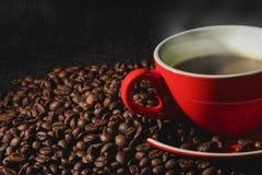 在红色杯子的咖啡和咖啡豆是背景 免版税库存图片