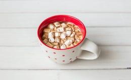 在红色杯子的热巧克力在白色木背景 免版税库存照片
