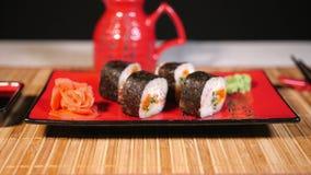 在红色板材的日本寿司有在竹背景的筷子的 影视素材