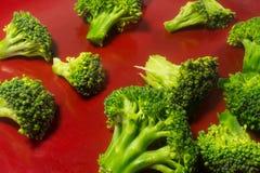 在红色板材的绿色Brocolli在白色背景 免版税库存照片