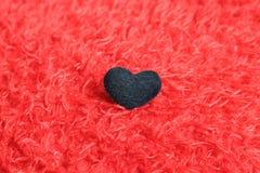 在红色枕头的黑心脏 免版税图库摄影