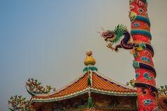 在红色柱子附近被包裹的中国龙五颜六色的雕象 义卖市场 图库摄影