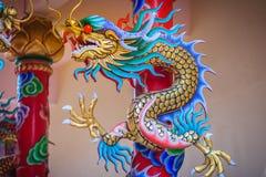 在红色柱子附近被包裹的中国龙五颜六色的雕象 义卖市场 免版税库存照片