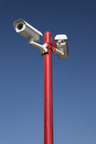 在红色柱子,被隔绝的蓝色的安全监控相机 库存照片