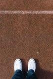 在红色格子呢运动场与两双鞋子,个人perspec的腿 库存图片