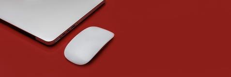 在红色桌背景的银色膝上型计算机 免版税库存图片