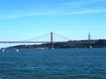 在红色桥梁ponte 25 de abril的海鸥飞行 库存照片