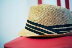在红色椅子的布朗德比盖帽 免版税库存照片