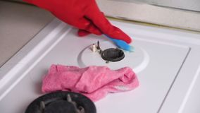 在红色橡胶手套洗涤肮脏的煤气炉的妇女的手与刷子和海绵 股票视频