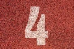 在红色橡胶跑马场的白色轨道数字,连续跑马场纹理在小室外体育场内 免版税图库摄影
