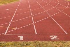 在红色橡胶跑马场的白色轨道数字,连续跑马场纹理在小室外体育场内 库存图片