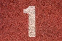 在红色橡胶跑马场的白色轨道数字,连续跑马场纹理在小室外体育场内 免版税库存图片