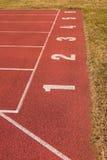 在红色橡胶跑马场的白色轨道数字,连续跑马场纹理在小室外体育场内 库存照片
