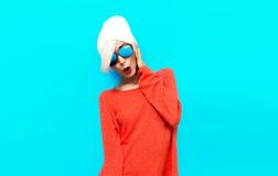 在红色毛线衣的画象性感的白肤金发的模型在蓝色背景 stu 免版税库存图片