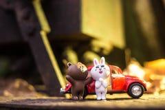 在红色汽车后的愉快的夫妇 免版税图库摄影