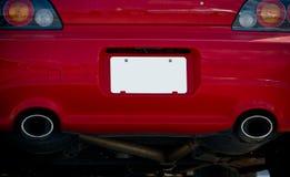 在红色汽车防撞器的空白的白色牌照 图库摄影