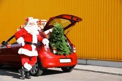 在红色汽车附近的地道圣诞老人有礼物盒的 免版税库存照片