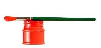在红色油漆罐头的绿色油漆刷 免版税库存图片