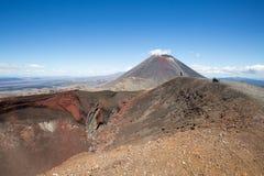在红色火山口旁边的远足者 免版税图库摄影