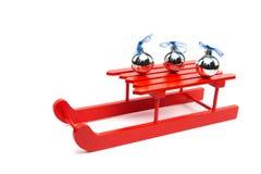 在红色爬犁的三个银色圣诞节球 免版税库存图片