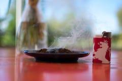 在红色狮子打火机旁边的抽烟的咖啡渣 免版税库存照片