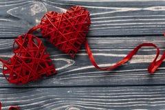 在红色玫瑰色华伦泰白色的概念重点 在黑rusti的时髦的两条红色心脏丝带 库存图片