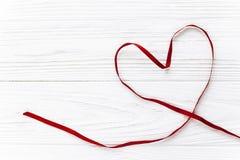 在红色玫瑰色华伦泰白色的概念重点 时髦的在白色木的丝带心脏平的位置 库存图片