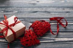 在红色玫瑰色华伦泰白色的概念重点 时髦的红色礼物和两条心脏丝带 免版税库存图片