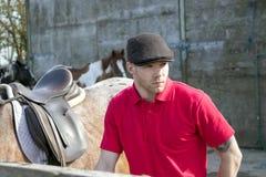 在红色球衣的英俊的马站立在他的被备鞍的马旁边的车手和flatcap 免版税库存照片