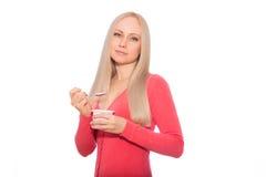 在红色的白肤金发的模型与匙子和酸奶 免版税图库摄影