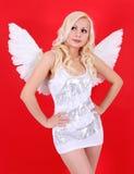 在红色的美丽的白肤金发的天使女孩 免版税库存图片
