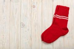 在红色的被编织的羊毛袜子在轻的木背景 图库摄影