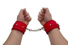 在红色皮革手铐的女性手 免版税库存图片