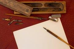 在红色皮革设置的古色古香的笔 免版税库存照片