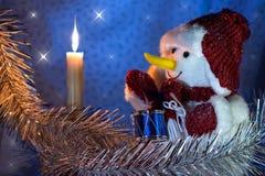 在红色盖帽的雪人有在一个灼烧的蜡烛附近的鼓的在蓝色背景 免版税库存图片