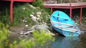 在红色码头和树枝4K射击附近的老蓝色小船 影视素材