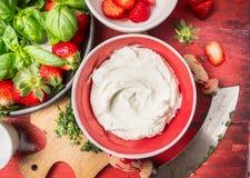 在红色碗用草莓,关闭的凝乳或乳脂干酪 免版税库存图片