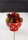 在红色碗的草莓有在豌豆的一个样式的在一张白色桌上 图库摄影