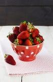 在红色碗的草莓有在豌豆的一个样式的在织品餐巾 免版税库存照片