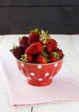在红色碗的草莓有在豌豆的一个样式的在织品餐巾o 免版税图库摄影