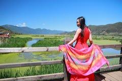 在红色礼服的亚洲中国秀丽享有平安和愉快的生活在云南鹿谷走的婚姻桥梁 免版税库存图片