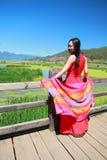 在红色礼服的亚洲中国秀丽享有平安和愉快的生活在云南鹿谷走的婚姻桥梁 库存图片