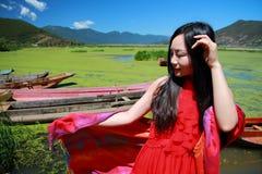 在红色礼服的亚洲中国秀丽在云南鹿谷草湖享有平安和愉快的生活 免版税库存照片